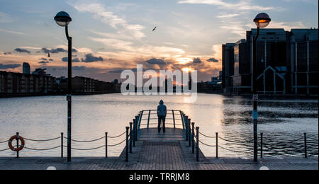 The silhouette of a young man in a hoody looking away from the camera at a dock in London's Docklands. - Stock Photo
