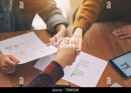 Closeup image of two people shaking hands in a meeting - Stock Photo