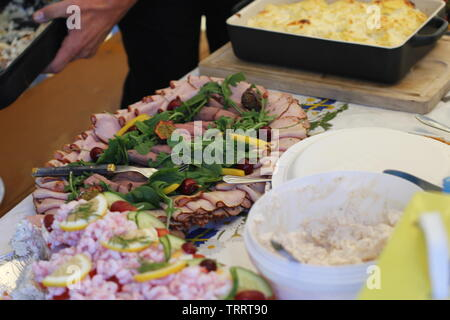 A table with food at a party in summer - Stock Photo