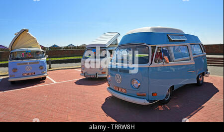 Three  Classic  Volkswagen  Camper Van  parked together with beach huts in the background. - Stock Photo