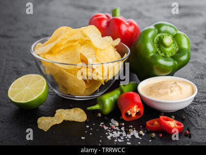 Glass bowl plate with potato crisps chips with onion flavour on black stone background. Red and green chilli peppers with lime and hot spicy sauce. - Stock Photo