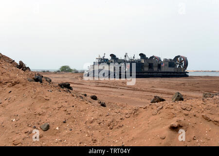 190609-N-WU565-109 – CAMP LEMONNIER, Djibouti  - A Landing Craft Air Cushion (LCAC) attached to the San Antonio-class amphibious transport dock ship USS Arlington (LPD 24), shuts-down gas turbines engines and deflates air cushion upon landing at Red Beach on base, June 9, 2019. The landing exercise is a requirement to certify the beach, demonstrate capabilities and readiness. Camp Lemonnier is an operational installation that enables U.S., allied and partner nation forces to be where and when they are needed to ensure security in Europe, Africa and Southwest Asia. (U.S. Navy photo by Mass Comm - Stock Photo