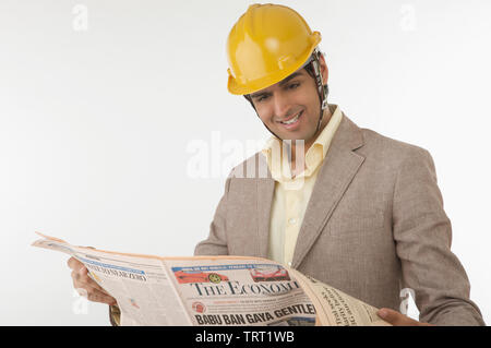 Indian male construction worker reading a newspaper - Stock Photo