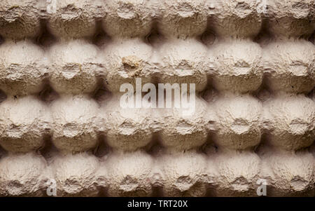 Top view surface sheet of empty cardboard egg crate or eggs carton box made of foam type brown color packing sheet. Old vintage look. Close up. Natura - Stock Photo