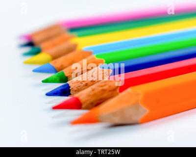 Standing Out From The Crowd Concept. Bunch of assorted multi colored pencils crayons in rainbow arrangement on white background, flat lay. Geometry pa