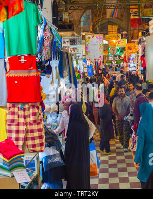 TEHRAN, IRAN - MAY 22, 2017: Crowd of people in row of Grand Bazaar with stalls of colorful clothes - Stock Photo