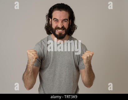Portrait of young happy and excited hipster man winning the lottery celebrating goal or having great success with proud face. In People success and Fa - Stock Photo