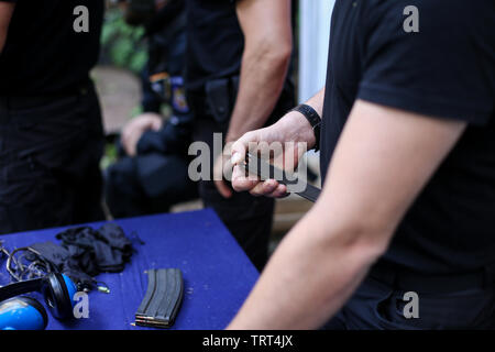 Man loading 9mm cartridges in a gun clip - Stock Photo