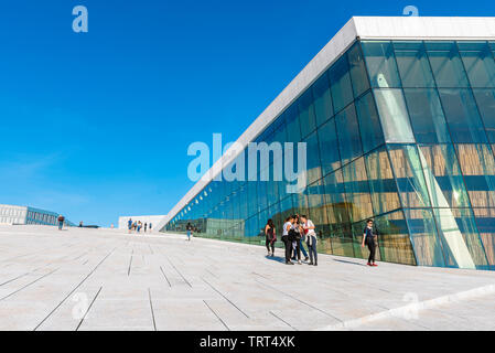 Opera House Oslo, view in summer of young people standing on the vast access ramp leading to the roof of the Oslo Opera House, Norway. - Stock Photo