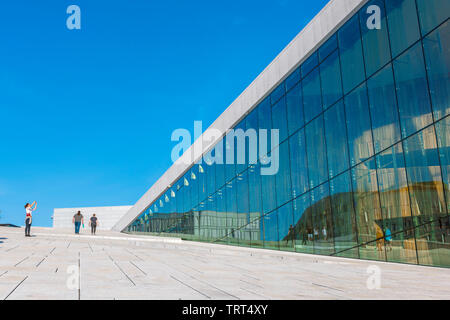 Oslo Opera House, view in summer of a tourist taking a photo on the vast access ramp leading to the roof of the Oslo Opera House, Norway. - Stock Photo