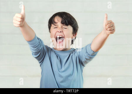euphoric child showing thumbs up on brick background - Stock Photo