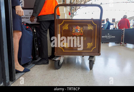 Pullman baggage luggage trolley with suitcases at the entrance to the Belmond Venice Simplon Orient Express departure lounge, London Victoria station - Stock Photo
