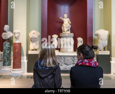 Girls sitting on a bench looking at classical sculptures at the Ashmolean Museum in Oxford - Stock Photo