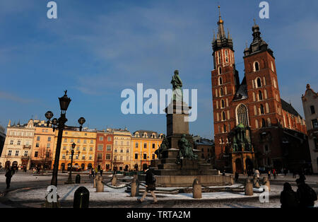 Poland. Krakow. Main Market Square. Adam Mickiewicz Monument in front of the St. Mary's Basilica, built in 14th century in Brick Gothic architecture style. - Stock Photo