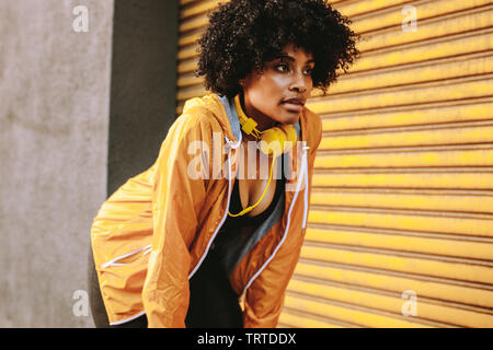 Fitness woman relaxing with hands on knees during workout standing outdoors. African woman in sportswear taking rest while training outdoors. - Stock Photo