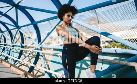 Fit young woman stretching her leg after a run in city. African woman in sportswear preparing for running workout. - Stock Photo