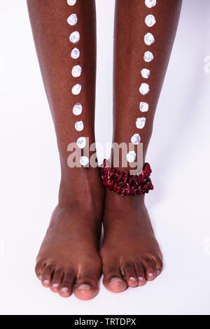 Legs of african woman with painted ritual pattern and bracelet on ankle - Stock Photo