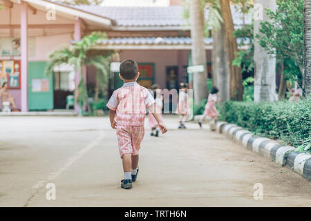 Back view of Boy followed girl friends on street to go to the classroom in school. - Stock Photo