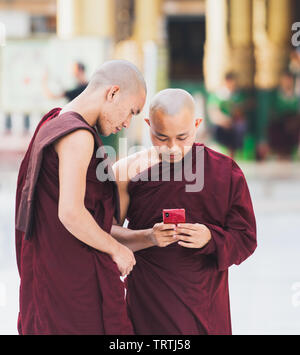 Yangon, Myanmar - March 2019: young Buddhist novice monks with gadgets in Shwedagon pagoda temple complex. Looking on telephone screen. - Stock Photo