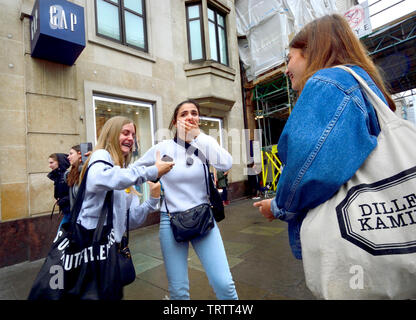 London, England, UK. Girls shopping in Oxford Street on a rainy day - Stock Photo