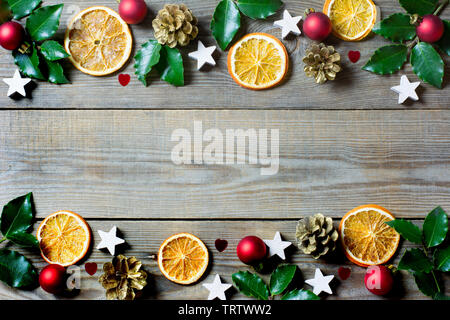 Christmas composition with orange slices, cones, holy, stars, red baubles and small  hearts on wooden background - Stock Photo