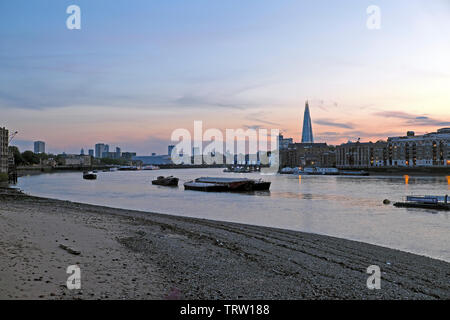 View towards the Shard skyscraper building, boats and barges on the River Thames at sunset in spring from South London England UK  KATHY DEWITT - Stock Photo