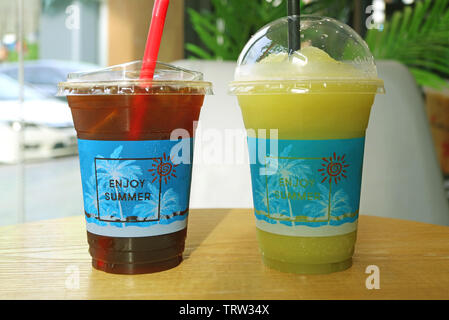 Iced coffee and icy sugarcane frappe in plastic cups ready for takeaway - Stock Photo