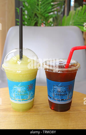Vertical image of icy sugarcane frappe and Iced coffee in takeaway plastic cups - Stock Photo
