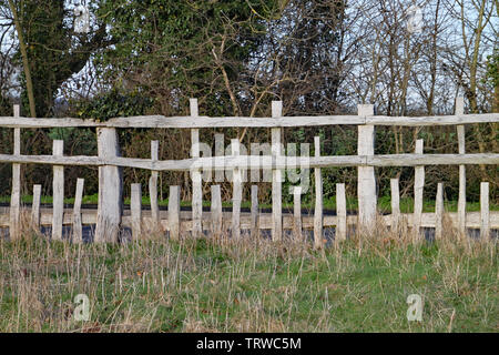 Unusual wooden fence with parallel horizontal rails and vertical posts of different lengths in a pattern - Stock Photo