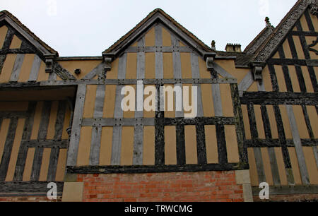 Part of a half timber framed building with ornate carvings on some of the facia boards - Stock Photo