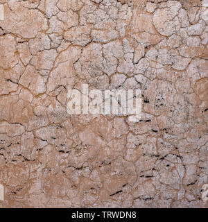 Cracked concrete old wall covered with beige cement surface as background. Textured background old cracked wall, close up. Old wall with cracks textur - Stock Photo