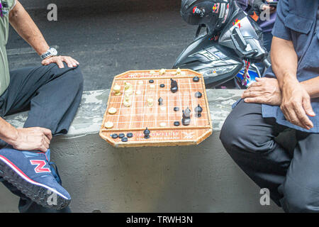 thai chinese men playing chinese checkers in Siam road Bangkok - Stock Photo