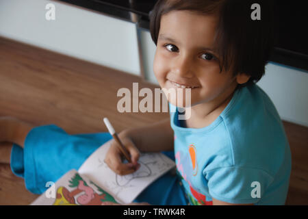 High angle view of a girl coloring in a book