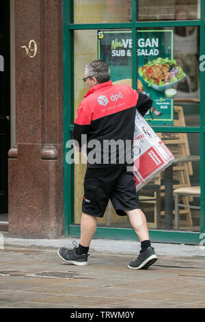 A DPD parcel courier delivery parcels to customers in Manchester city centre, UK