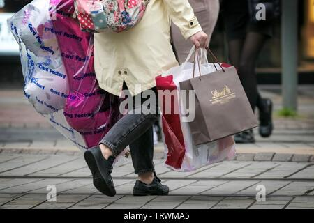 A woman carries multiple carrier bags after a shopping trip through the streets of Manchester, UK - Stock Photo