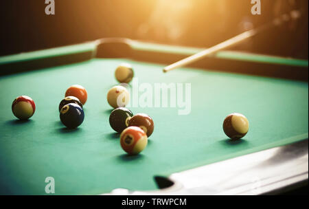 A human aims a cue at billiard balls of different colors lying on a green billiard table. - Stock Photo