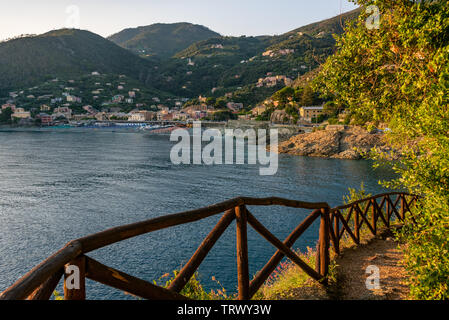 Mountain path, wooden fence on the side of  the mountain leading to the Mediterranean sea. In the distance, the beach of Bonassola, Liguria, - Stock Photo