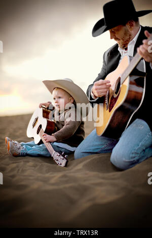 Father and his young son holding guitars while wearing cowboy hats and sitting on a sandy beach. - Stock Photo