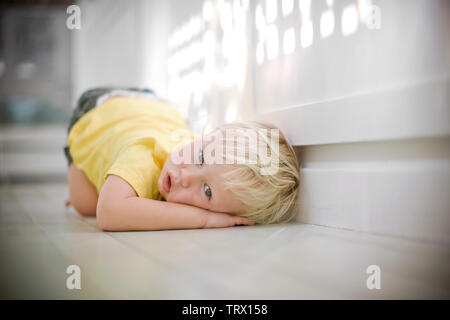 Portrait of a young boy resting his head on his hand while curled up on the floor. - Stock Photo
