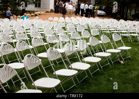 Rows of empty white folding chairs in a backyard. - Stock Photo
