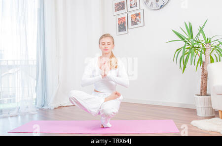 Beautiful woman is practicing yoga at home on yoga mat, girl doing Half Lotus Toe Balance exercise, Sitting in squat position - Stock Photo