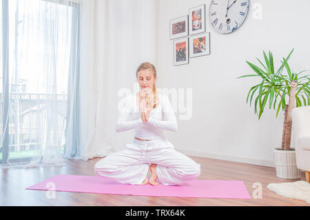 Yoga time. Beautiful woman is practicing yoga at home on yoga mat - Stock Photo