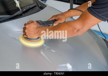 Hands with Machine polisher in auto repair. - Stock Photo