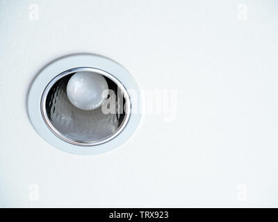 Close-up LED ceiling light. Downlight with light bulb on white ceiling background with copy space. - Stock Photo