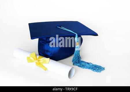 Blue graduation cap or mortarboard with blue tassel and diploma with yellow ribbon, isolated on white background. - Stock Photo