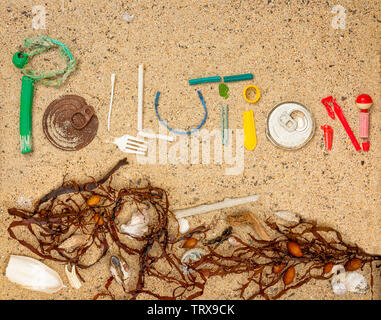 Pollution text made from real single use plastic rubbish found on beach with shells, seaweed and natural beach debris - Stock Photo