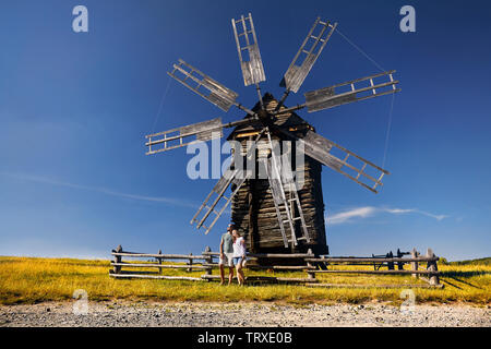 Couple of tourist posing near old traditional wind mill in National architecture museum in Pirogovo, Kiev, Ukraine - Stock Photo