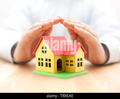 Colorful toy house covered by hands - Stock Photo