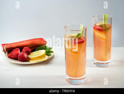 Homemade organic lemonade with strawberries, rhubarb and and mint  in two glasses on the wooden background.  Healthy natural  flavored drink. - Stock Photo