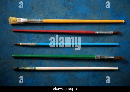 Paintbrushes on a blue table. Stock Photo